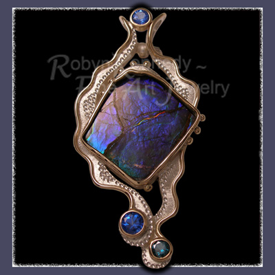 Freeform Ammolite Pendant Accented with Glacier Blue and Evergreen Diffused Topaz set in 10 Karat Yellow Gold and Sterling Silver